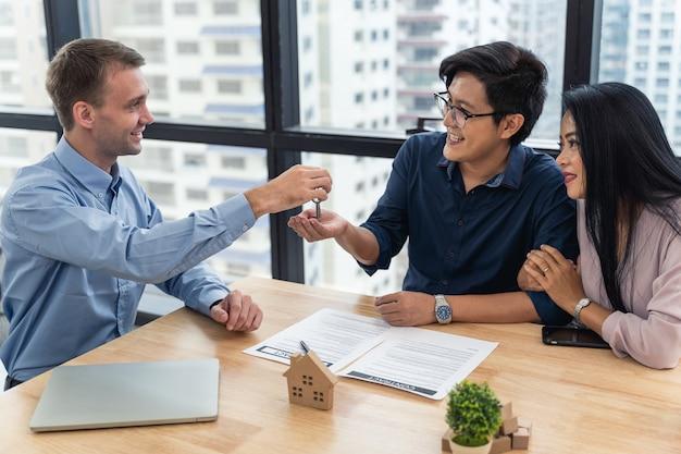 Het aziatische jonge paar ondertekende de aankoop of de huur van het contacthuis in bureau van makelaar en verkoopvertegenwoordiger die sleutel van nieuw huis aan jong paar in bureau geven