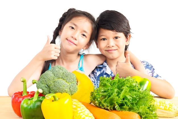 Het aziatische jongen en meisjes tonen geniet van uitdrukking met verse kleurrijke groenten