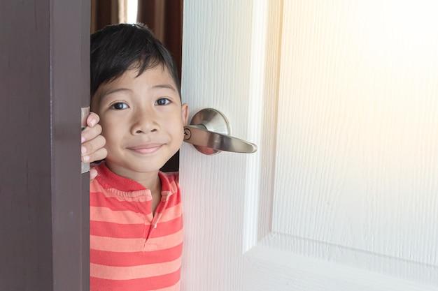 Het aziatische jongen glimlachen, opende thuis de witte deur