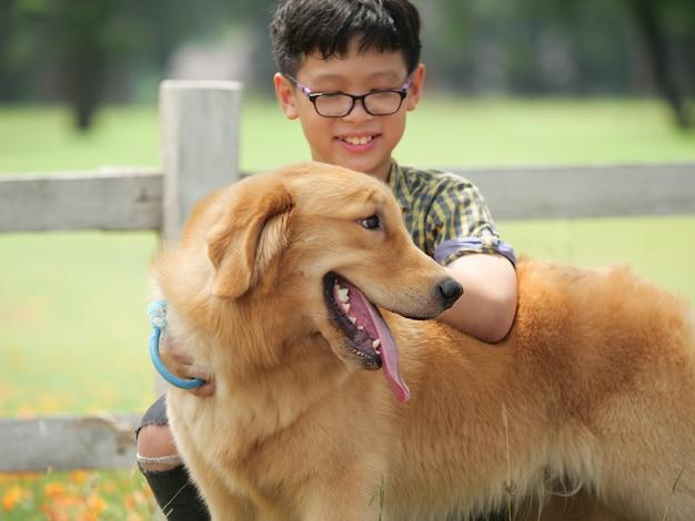 Het aziatische jongen spelen met gouden retreiver van de puppyhond in park