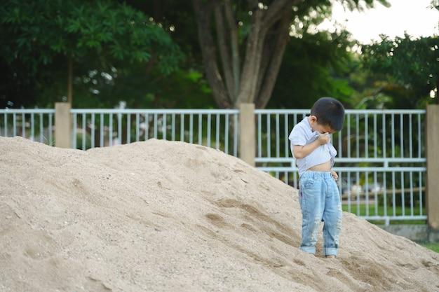 Het aziatische jongen spelen met zand en stuk speelgoed bij openbaar park