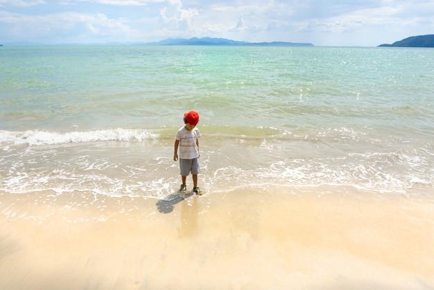 Het aziatische jongen spelen op het overzees van thailand en het witte zandstrand