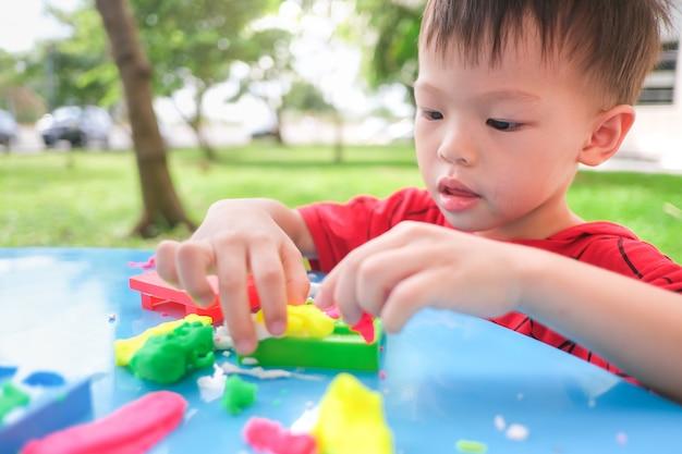 Het aziatische kind dat van de peuterbaby pret heeft die kleurrijke boetseerklei speelt