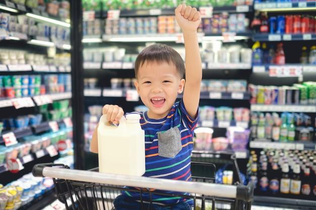 Het aziatische kind zit in boodschappenwagentje kies zuivelproduct in kruidenierswinkelopslag