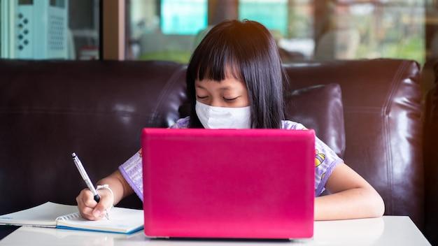 Het aziatische kindmeisje die huiswerk bestuderen en gezichtsmasker dragen tijdens haar online les thuis voor beschermt 2019-ncov of covid 19 virus, online onderwijsconcept. 16: 9 stijl