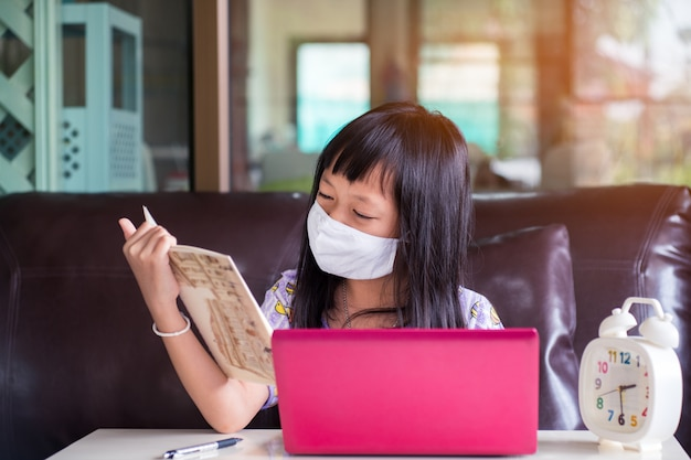 Het aziatische kindmeisje die huiswerk bestuderen en gezichtsmasker dragen tijdens haar online les thuis voor beschermt 2019-ncov of covid 19 virus, online onderwijsconcept.