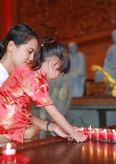 Het aziatische kindmeisje in traditionele kleding steekt de vereringskaarsen aan bij chinese tempel