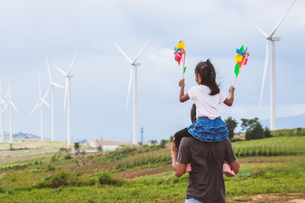 Het aziatische kindmeisje spelen met windturbine en het berijden op de schouders van de vader