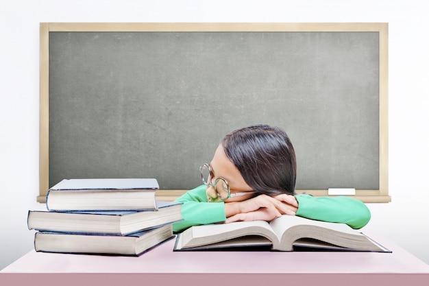 Het aziatische leuke meisje met glazen valt in slaap op boek op het bureau