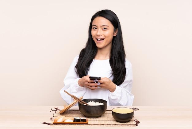 Het aziatische meisje dat van de tiener aziatisch voedsel eet dat op beige muur wordt verrast verraste en een bericht verzendt