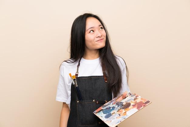 Het aziatische meisje dat van de tienerschilder omhoog terwijl het glimlachen kijkt