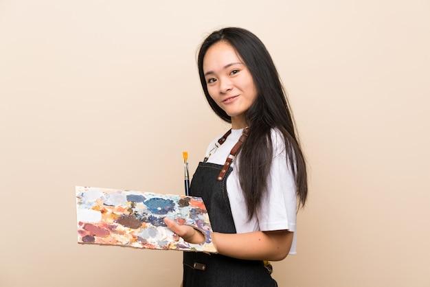 Het aziatische meisje dat van de tienerschilder veel glimlacht