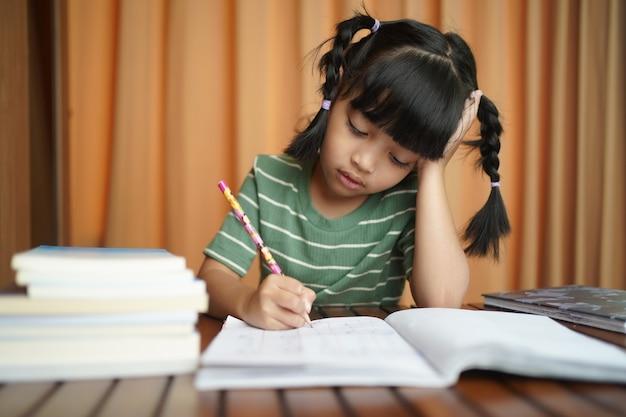 Het aziatische meisje dat van het studentenkind op het document boek schrijft.