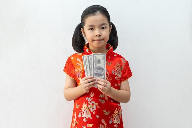 Het aziatische meisje draagt cheongsam en neemt bankbiljet in chinees nieuw jaar
