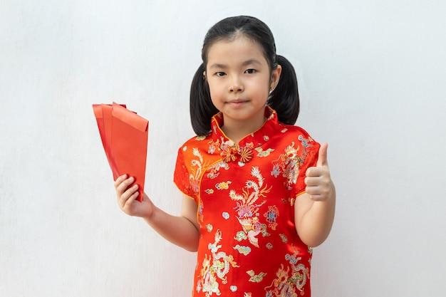Het aziatische meisje draagt cheongsam en neemt rode enveloppen in chinees nieuw jaar