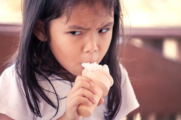 Het aziatische meisje eet roomijskegel met boze gezichtsuitdrukking in uitstekende kleurentoon