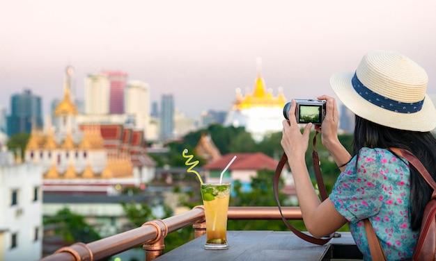 Het aziatische meisje ontspant op de dak hoogste bar in de stad van bangkok en geniet van meningspunt van loha prasat