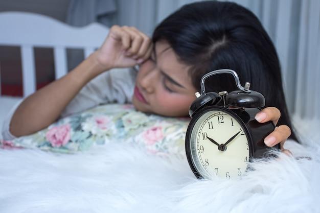 Het aziatische meisje op wit bed ontwaakt laat bekijkt wekker in ochtend