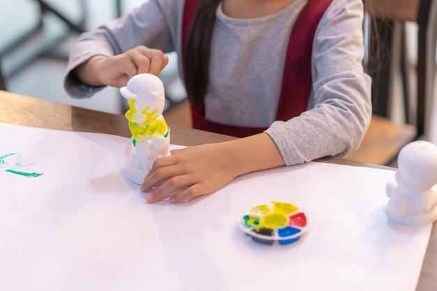 Het aziatische meisje schildert een pop in art-klaslokaal, voor creativiteitconcept