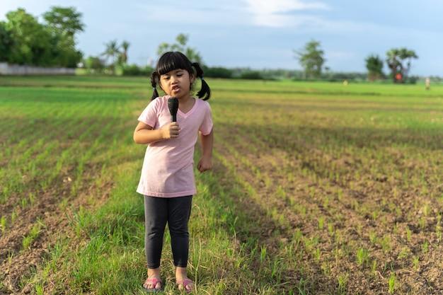 Het aziatische meisje staat en zingt het midden van de velden, genietend en heeft plezier.