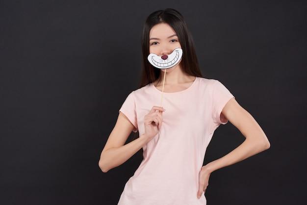 Het aziatische meisje stelt met geïsoleerde de glimlach van cheshire.