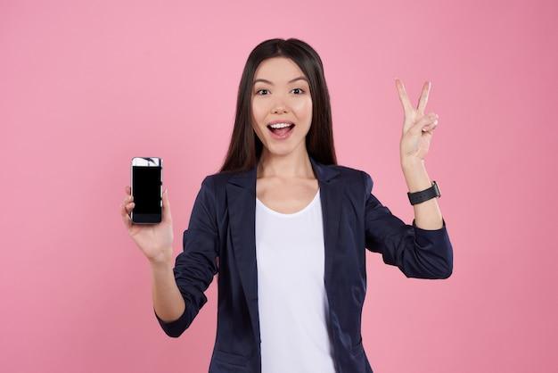Het aziatische meisje stelt met geïsoleerde telefoon