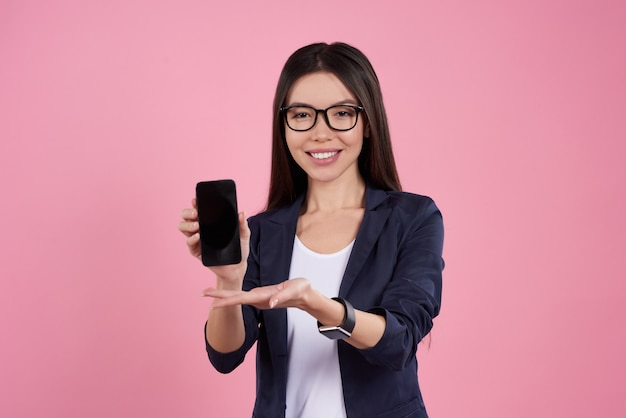 Het aziatische meisje stelt met zwarte telefoon in glazen.