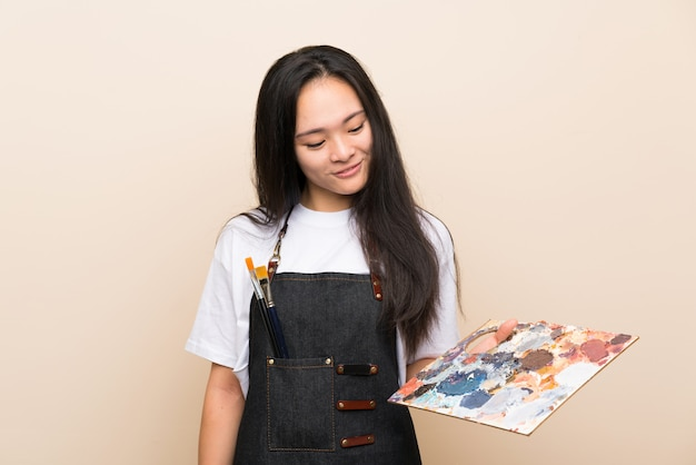 Het aziatische meisje van de tienerschilder met gelukkige uitdrukking