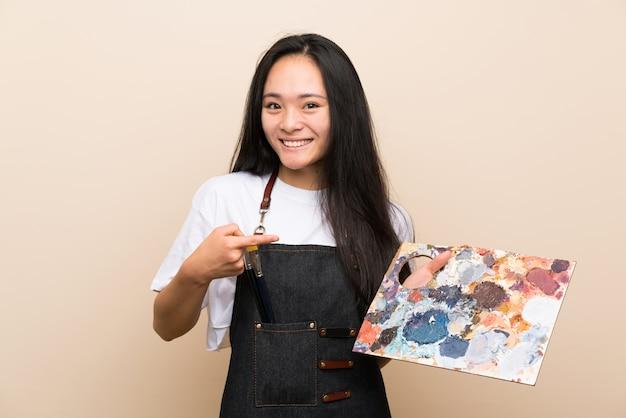 Het aziatische meisje van de tienerschilder met verrassingsgelaatsuitdrukking