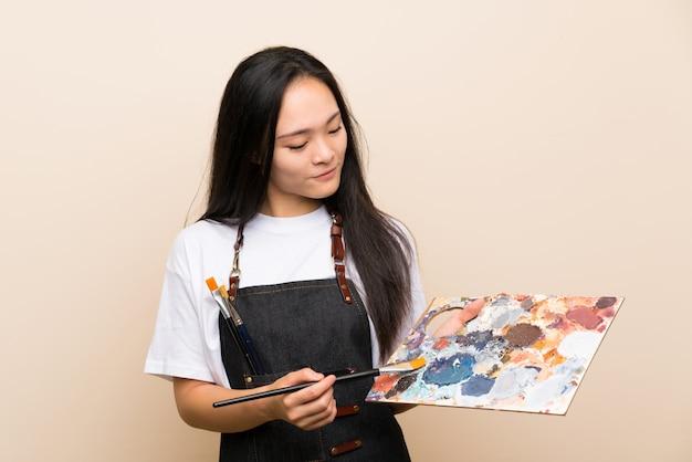 Het aziatische meisje van de tienerschilder over geïsoleerde muur