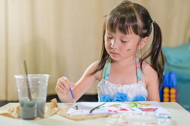 Het aziatische meisjekind schilderen met penseel en kleurrijke verven op papier die het werk van het schoolhuis doen