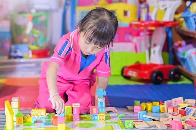 Het aziatische meisjekind spelen in ruimtespeelgoed voor kinderen ontwikkelt zich in kleuterschool, ook bekend als kleuterschool