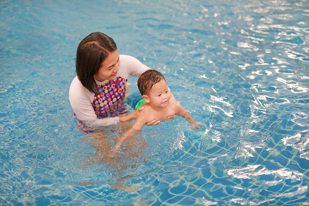 Het aziatische moeder en babyjongen ontspannen in zwembad
