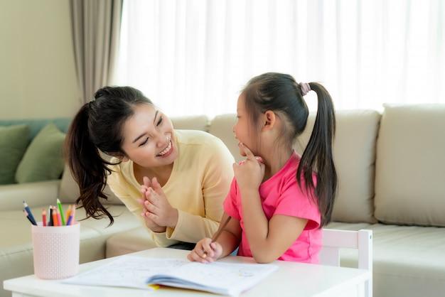 Het aziatische moeder spelen met haar dochter die samen met kleurenpotloden thuis bij lijst in woonkamer trekken. ouderschap of liefde en binding expressie concept.