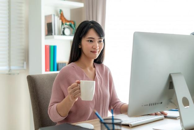 Het aziatische mooie jonge vrouwenwerk vanuit huis die aan computer werken en koffie drinken