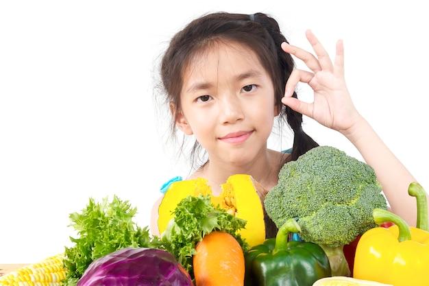 Het aziatische mooie meisje tonen geniet van uitdrukking met verse kleurrijke groenten