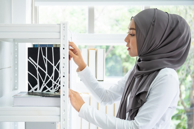 Het aziatische moslimonderneemster kiezen boeken op boekenplank in haar bureau, moslimstudent.