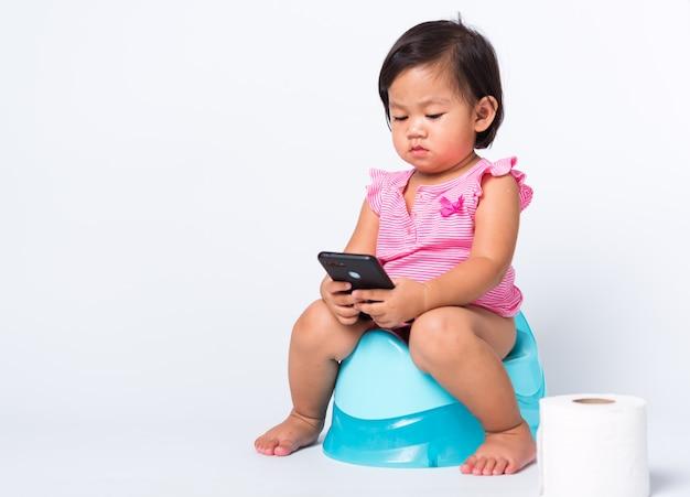 Het aziatische onderwijs die van het kindmeisje op het zitten op kamerpot opleiden