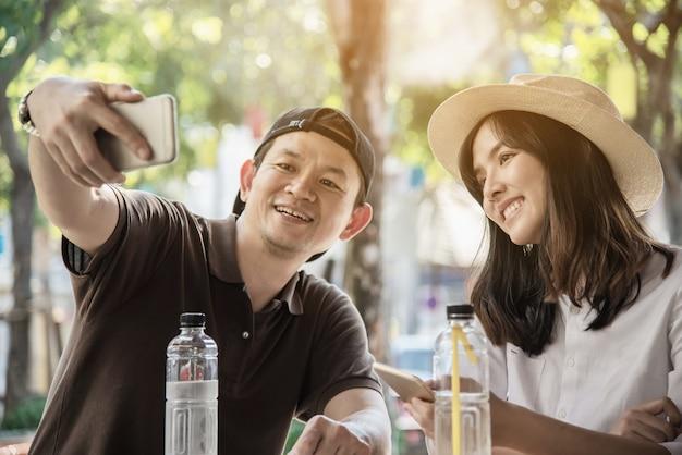 Het aziatische paar geniet van reizende zitting bij koffiewinkel