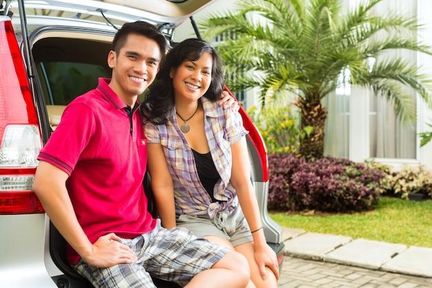 Het aziatische paar is gelukkig vooraan de auto
