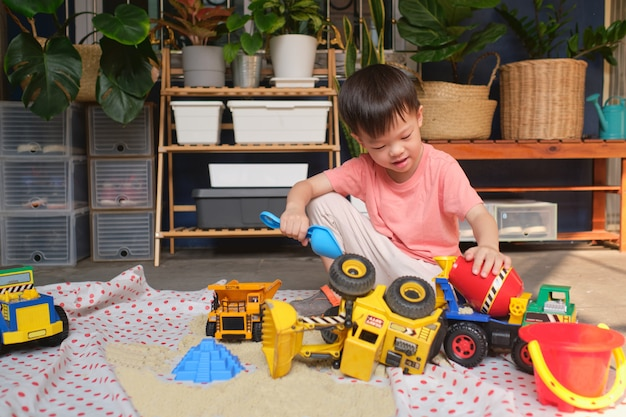 Het aziatische peuterjongen spelen met kinetisch zand thuis, kind het spelen met stuk speelgoed bouwmachines, montessori-onderwijs, creatief spel voor jonge geitjesconcept