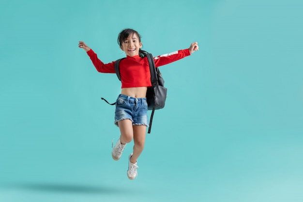 Het aziatische schoolmeisje springt. ze is gelukkig.