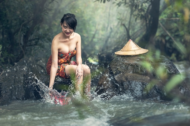 Het aziatische sexy vrouw baden in kreek, thailand