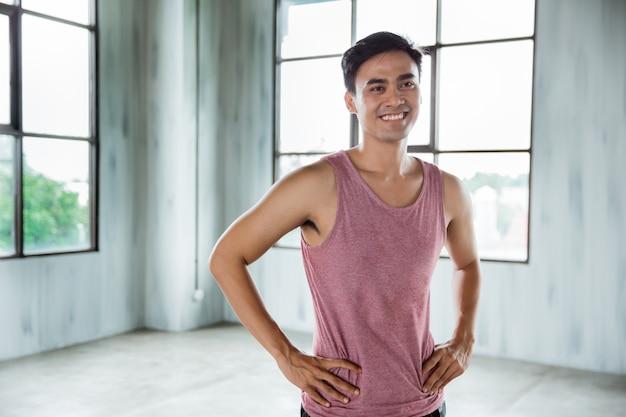Het aziatische sportmens glimlachen en zijn handen op heupen