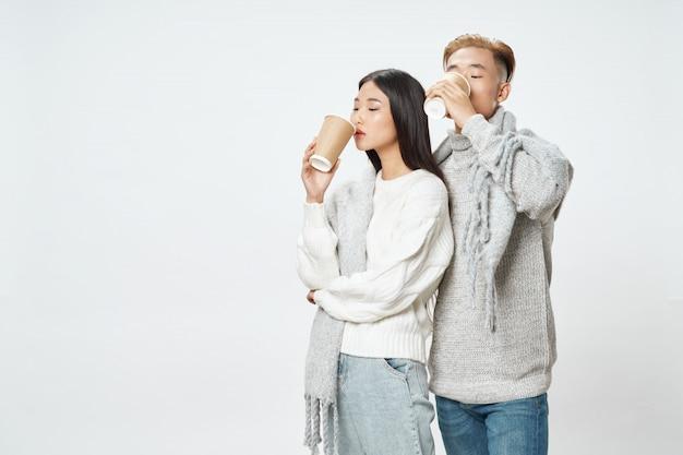 Het aziatische vrouw en man paar stellen met de winterkleren en koffiekoppen