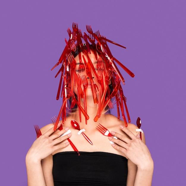 Het aziatische vrouw stellen met rood plastic vaatwerk op haar