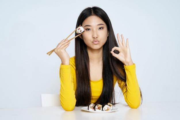 Het aziatische vrouw stellen met voedselportret, sushi