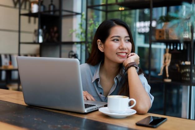 Het aziatische vrouw werken en drinkt koffie in koffie met laptop computerglimlach en het gelukkige werk