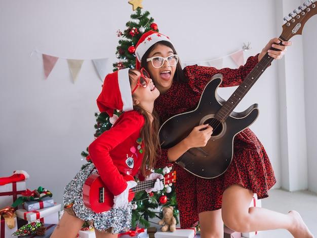 Het aziatische vrouwen en jonge geitje vieren kerstmis door de gitaar binnenshuis te tokkelen