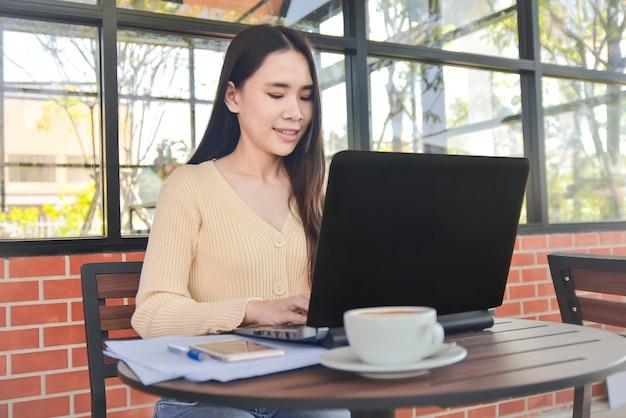 Het aziatische vrouwen typen op computer het werkende vrouwenwerk van huis